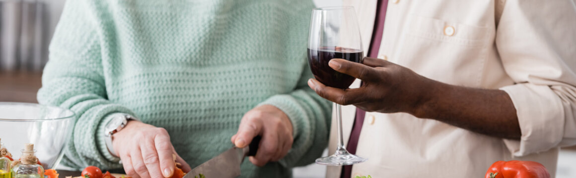 partial view of african american senior man holding glass of wine near wife, banner