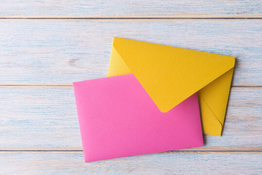 Plank pink card and yellow envelope on light wooden background