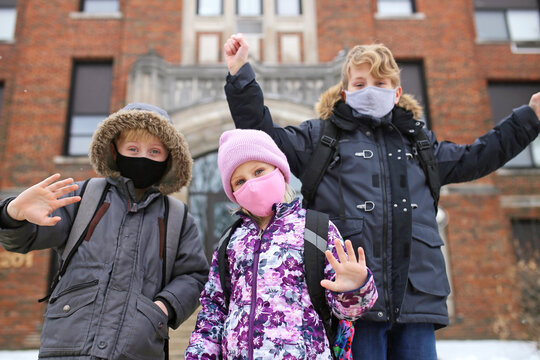 Happy Children with Covid Facemasks in Front of Brick School Building