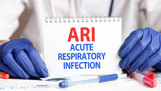 Doctor holding a tablet with text: ARI. ARI - Acute Respiratory Infection, medical concept.