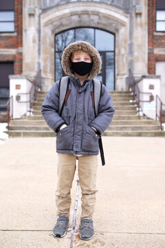 Third Grade Boy Child in Covid Face Mask Outside Elementary School Education Building