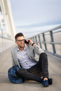 Happy young businessperson talking on smartphone sitting and relaxing on the bridge. Joyful yuppie or young entrepreneur outside