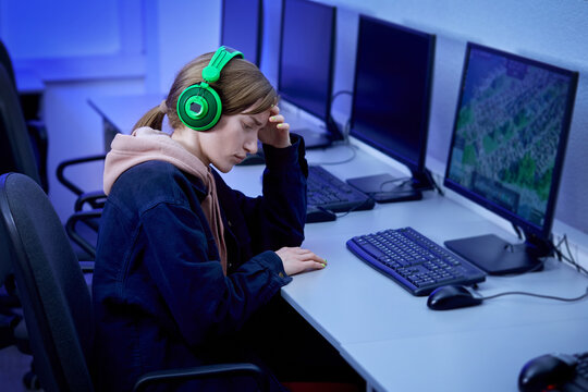 A young beautiful woman is upset about losing a video game. Hand supports the head. Esports player. Computer room with portable computers.