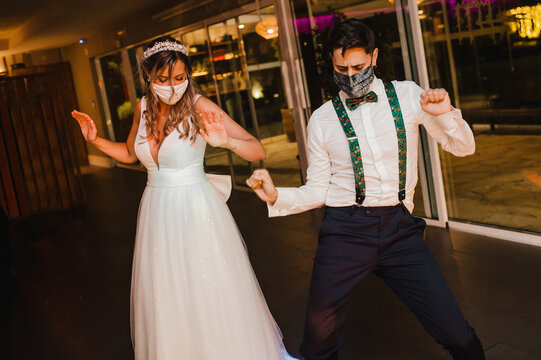Young couple with surgical masks dancing on their wedding