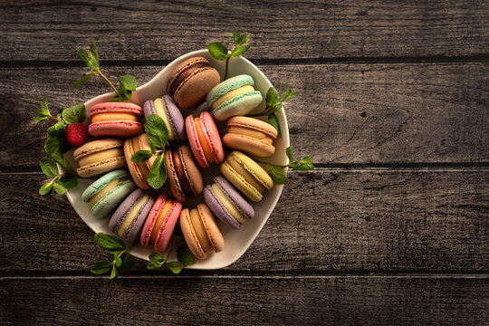 Colorful macaroni cakes. Small French cakes. Sweet and colorful French macarons are plates in the shape of a heart. Top view. Copy Space