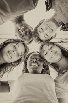 Upward view of teenagers smiling together in a circle. Multi ethnic friends happy, freindship and antiracism concept