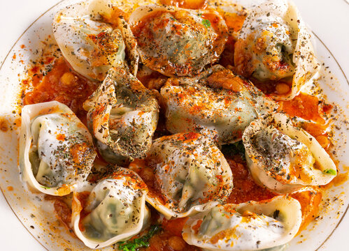 Close-up of Afghan Mantu covered with savory spices and herbs