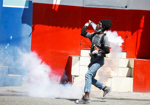 A man throws a tear gas canister back at the police during a protest against Haiti's President Jovenel Moise, in Port-au-Prince