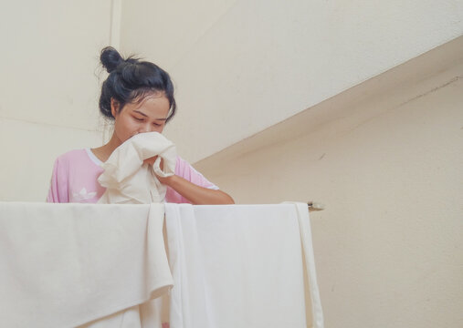 Woman Smelling Laundry While Standing In Balcony