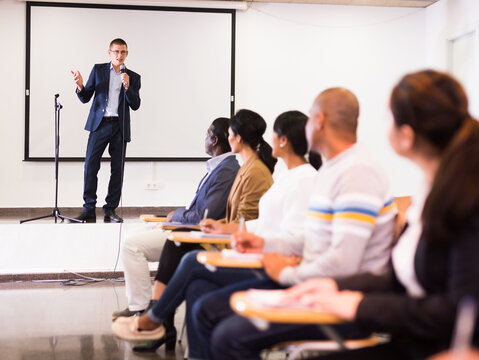Confident lecturer standing with microphone on stage in conference room, speaking to businesspeople at seminar