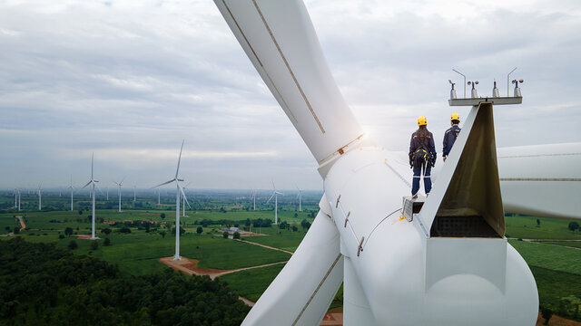 Inspection engineers standing on top of a wind turbine for Background Image.