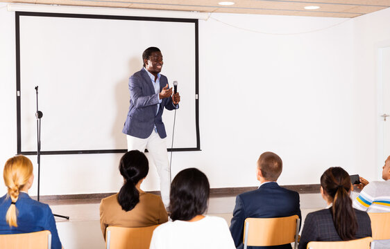 Excited african american preacher giving motivational speech to business people from stage in conference hall