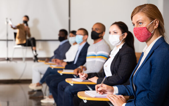 Young focused woman in protective face mask sitting and listening to speaker at business conference