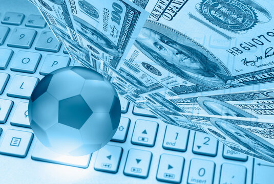 Crystall soccer ball on the laptop keyboard with dollar - Sport and technology concept