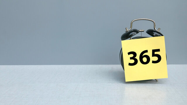 An alarm clock with a sticky note written with 365 represent days in a year on grey background with copy space.