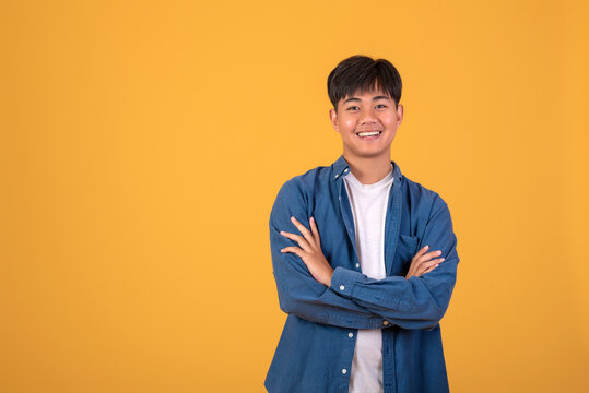 On orange background With a young Asian man Happy standing.