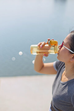 Young Woman Drinking Water By Lake