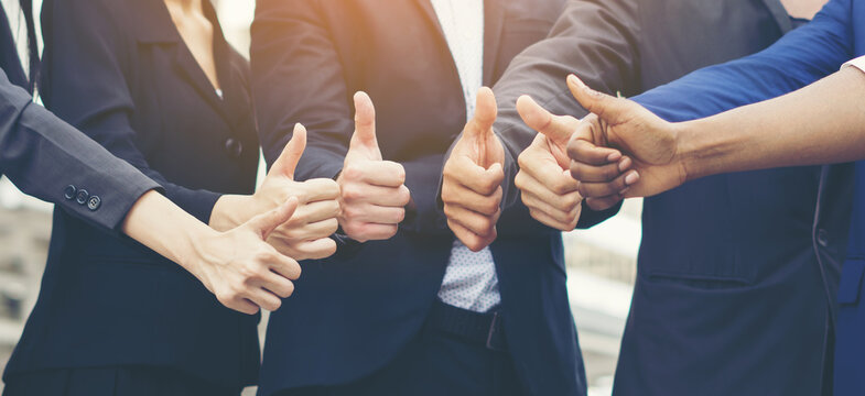 Midsection Of Business Partners Gesturing Thumbs Up Sign While Standing Side By Side