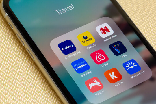 Portland, OR, USA - Feb 10, 2021: Assorted travel apps are seen on an iPhone on a lounge chair - Booking.com, Expedia, Hotels.com, Priceline, Airbnb, Vrbo, Hopper, KAYAK, and Skyscanner.