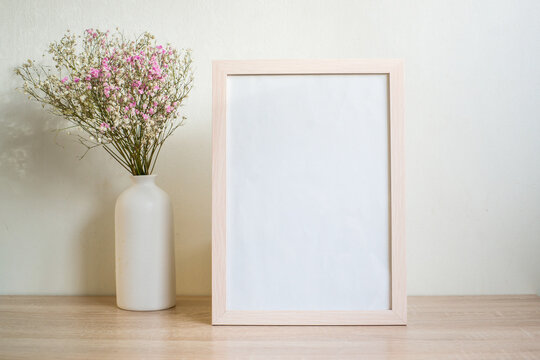 Portrait white picture frame mockup on wooden table. Modern ceramic vase with gypsophila.  White wall background. Scandinavian interior. Vertical.