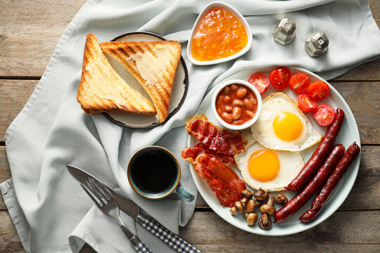 Traditional English breakfast with fried eggs on wooden background