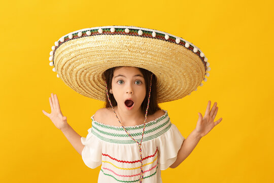 Surprised Mexican girl in sombrero hat on color background