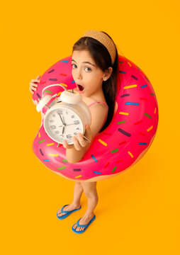 Surprised little girl in swimsuit, with alarm clock and inflatable ring on color background