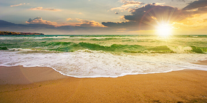 sea tide on a cloudy sunrise. green waves crashing golden sandy beach in morning light. storm weather approaching. summer holiday concept