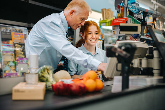 Grocery store manager training a new cashier
