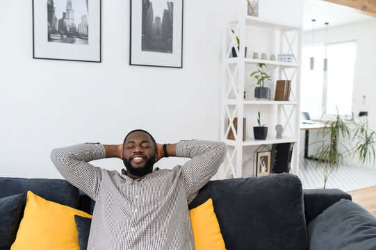Satisfied young african man resting on comfortable couch in white cozy modern living room, holding hands behind head, millennial hipster guy enjoy no stress life on sofa at home with his eyes closed