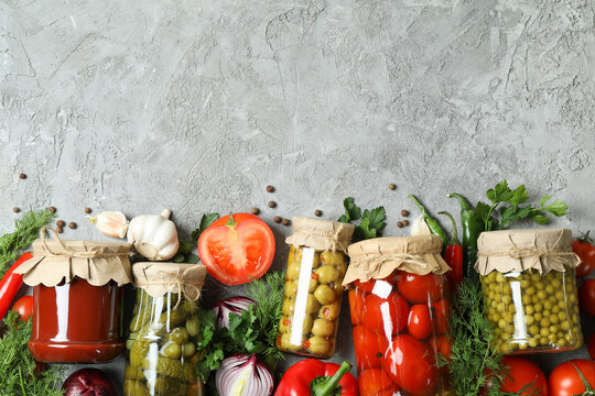 Different canned food and ingredients on gray background