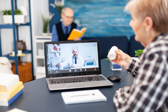 Senior pensioner listening doctor talking about treatment during online consultation. Elderly woman discussing with healthcare practitioner in the course of remote call and husband is reading a book