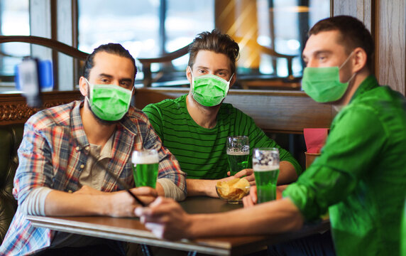 friendship, health and st patrick's day concept - male friends wearing face protective medical mask for protection from virus disease drinking green beer and taking selfie with smartphone at bar