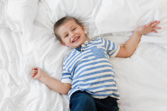 Overhead portrait of happy young boy lying on bed