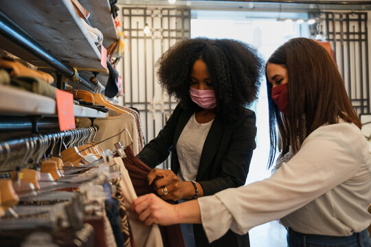 Two friends in clothes shop look and choose clothes to buy wearing protective face masks during the Coronavirus Covid-19 pandemic - Sales assistant helps a customer in the choice in the store