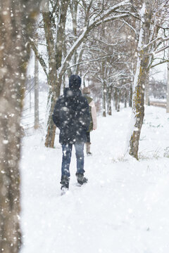 two people walk on a snow-covered path in winter, a teenage boy and a girl, a snowstorm