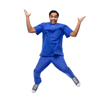 healthcare, profession and medicine concept - happy smiling indian doctor or male nurse in blue uniform jumping in air over white background