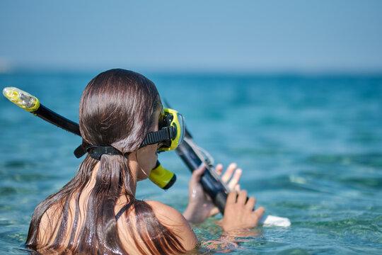 A woman in a bikini hunts with a crossbow