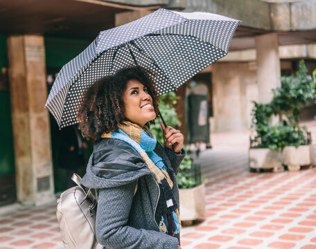 Afro American woman in coat and umbrella smiles while looking up