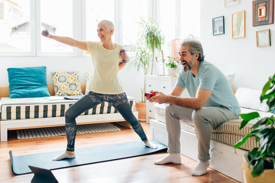 Senior woman doing exercises while senior man playing video games on couch