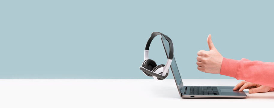 Side view of slim laptop and like thumb up hand. wireless headphones on grey desk. Blue background. Distant learning. working from home, online courses support. Audio podcast. vlogger blogger banner