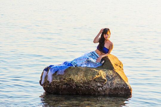 Woman In Mermaid Costume Sitting On Rock In Lake