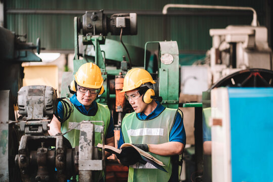 Work at factory.Two Asian workers man team working together in safety work wear with yellow helmet using Manual book.in factory workshop industry meeting professional