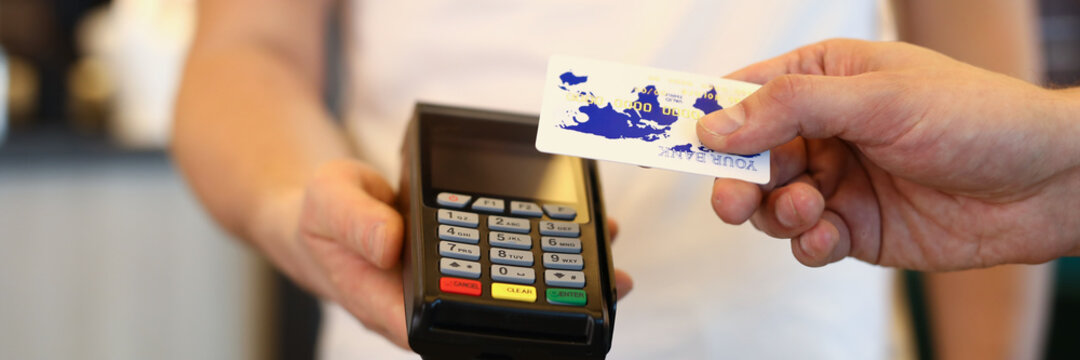 Man applies card to terminal and makes payment. Online shopping concept