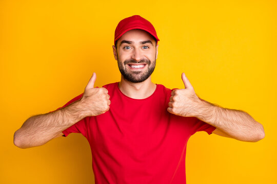 Photo of cute funny guy courier dressed red clothes showing thumbs up two hands isolated yellow color background