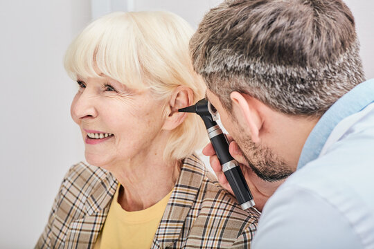 Elderly woman during ear exam at a hearing clinic. Audiologist examining elderly patient ear using otoscope