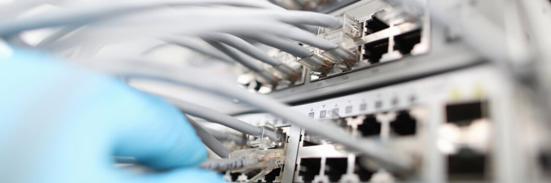 Technician checks the quality of internet connection against background cable hub close-up. Computer bad network cabling concept