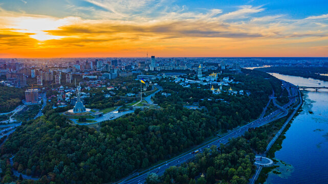 Aerial view to the  Beautiful landscape city Kiev with a Dnepr river while sunset. Top view to the city Kiev in the summer. Beautiful city Kiev while sunset.
