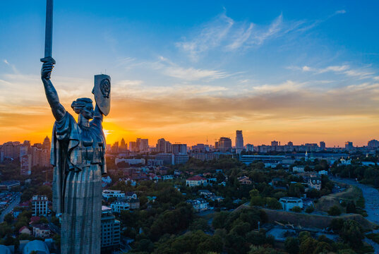 Aerial view to the Motherland statue in the Kiev while  summer sunset. The well-known landmarks in Kyiv. Historical monument of Soviet union. Beautiful city Kiev while sunset.