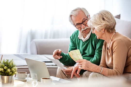 Senior couple sitting at a table at home and going through their household finances using a laptop. Senior couple going through bills while using laptop at home.